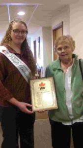 The Maple Ambassador presents Mrs. Livingston a Hall of Fame plaque, which she accepts  on behalf of her husband Dave Livingston