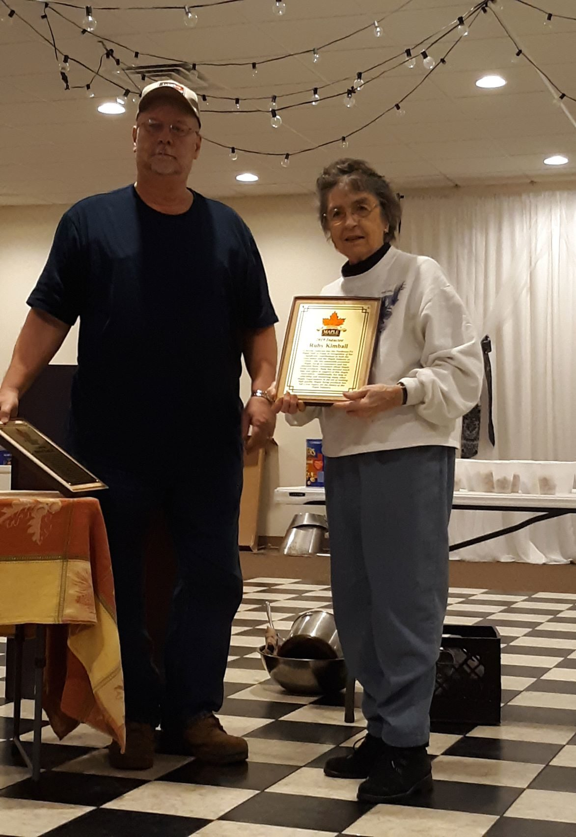 Ruby Kimball accepts a Hall of Fame Induction plaque on behalf of her husband Burton Kimball
